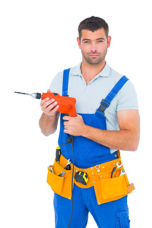 Portrait of confident male carpenter in overall holding drill machine on white background photo