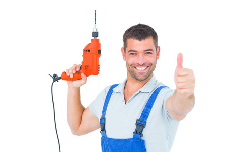 Portrait of smiling repairman with drill machine gesturing thumbs up on white background photo