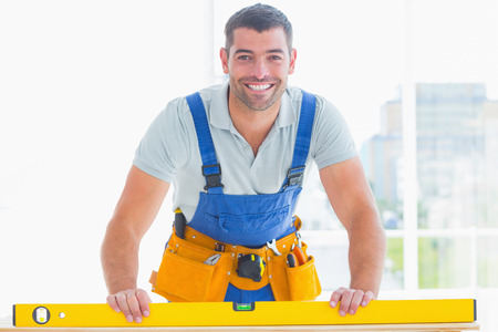 Portret van lachende klusjesman met waterpas in heldere kantoor