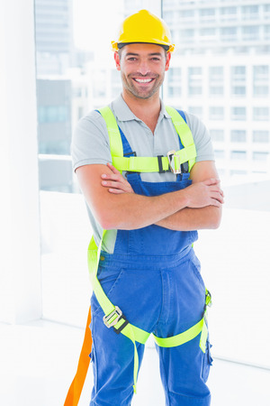 safety harness: Portrait of happy manual worker wearing safety harness standing arms crossed in bright office Stock Photo
