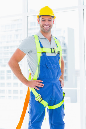 safety harness: Portrait of construction worker wearing safety harness in bright office