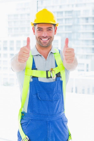 safety harness: Portrait of construction worker wearing safety harness while gesturing thumbs up in bright office