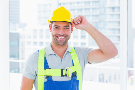 yellow hard hat: Portrait of happy manual worker wearing yellow hard hat in bright office