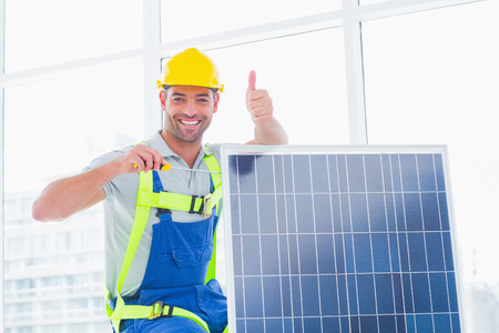 tightening: Portrait of smiling male worker tightening solar panel while gesturing thumbs up in bright office