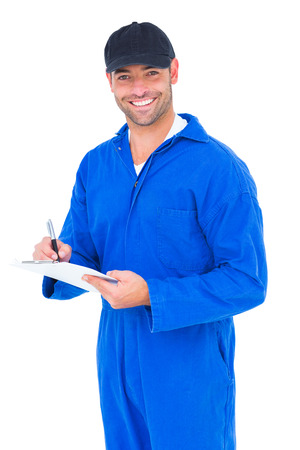 Portrait of smiling handyman in blue overall writing on clipboard over white background photo