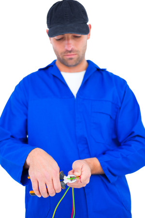 Male electrician cutting wire with pliers over white background photo