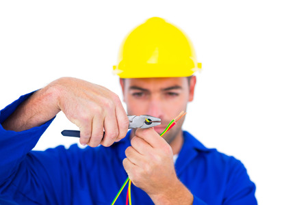 Male electrician wearing hard hat while cutting wire with pliers over white background photo