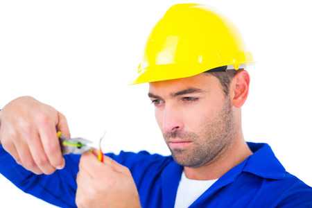 Electrician wearing hard hat while cutting wire with pliers over white background photo