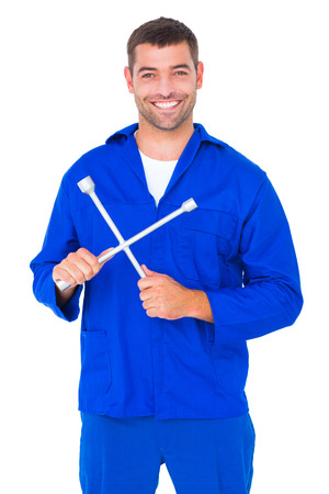 lug: Portrait of smiling male mechanic holding lug wrench on white background