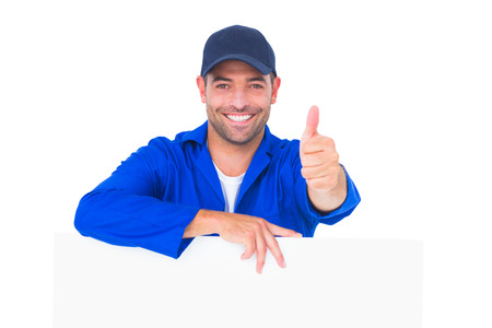 Portrait of male mechanic with blank placard gesturing thumbs up on white background