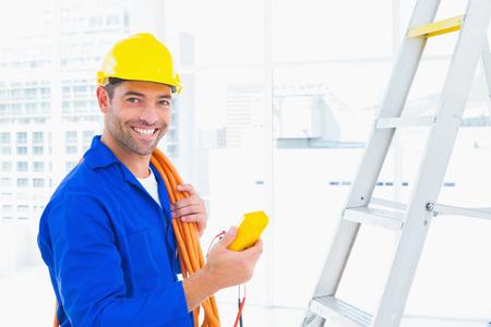 Portret van het glimlachen mannelijke elektricien met multimeter in heldere kantoor