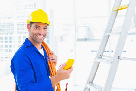 Portrait of smiling male electrician holding multimeter in bright office Foto de archivo