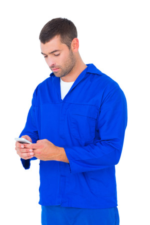 Male mechanic text messaging through mobile phone on white background photo
