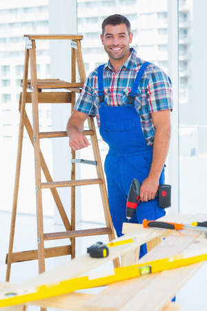 power drill: Portrait of smiling male carpenter with power drill standing by ladder at construction site