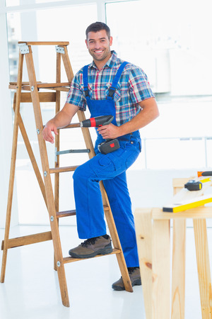 Full length portrait of confident carpenter with power drill climbing ladder at construction site photo