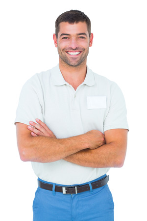 crossed arms: Portrait of smiling male technician standing arms crossed on white background Stock Photo