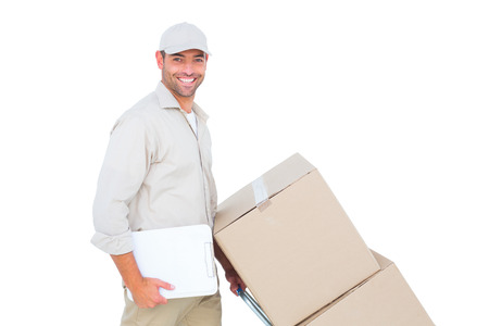 Portrait of happy delivery man pushing trolley of boxes on white background Reklamní fotografie - 38186752
