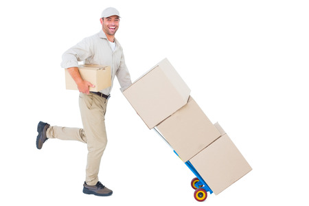 service occupation: Full length portrait of happy delivery man with trolley of boxes running on white background