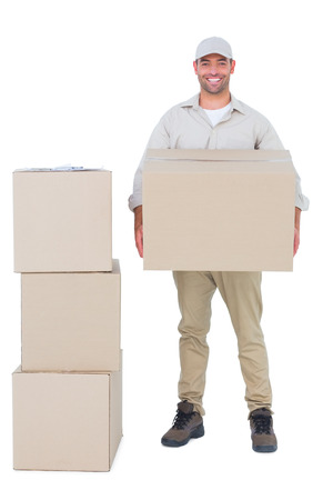 Full length portrait of courier man carrying cardboard box on white background Stock Photo
