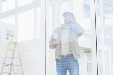 Male architect with blueprints using mobile phone in office photo