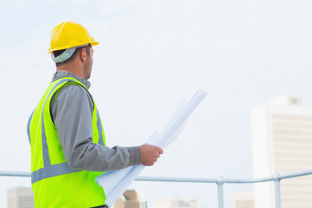 protective workwear: Side view of male architect in protective workwear holding blueprints outdoors