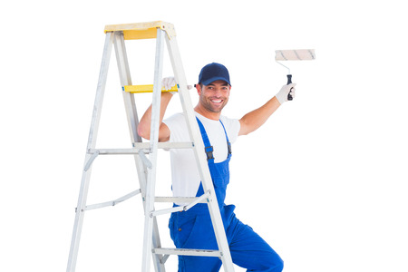 redecorating: Portrait of happy handyman on ladder while using paint roller on white background