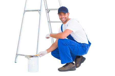 paint can: Full length portrait of happy handyman crouching by paint can on white background Stock Photo