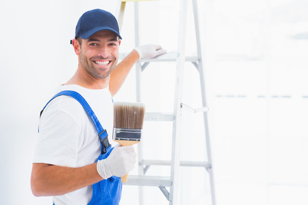 redecorating: Portrait of happy handyman with paintbrush while climbing ladder at home Stock Photo