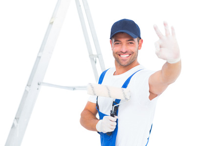 redecorating: Portrait of happy handyman with paint roller gesturing okay on white background