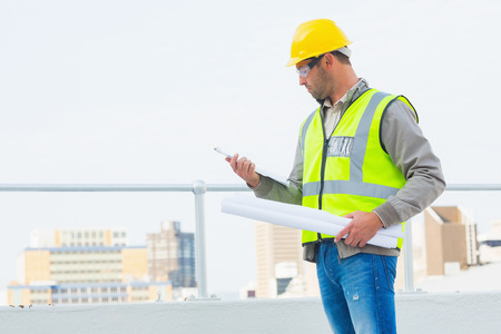 contractor: Male architect with blueprints reading clipboard outdoors