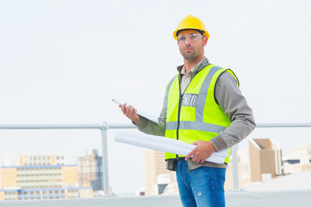 Male architect in protective clothing holding blueprints and clipboard outdoors Stock Photo
