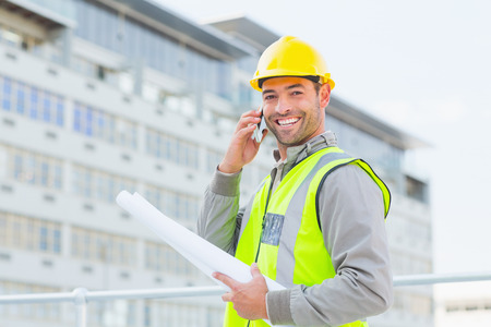 Portrait of smiling male architect with blueprints talking on mobile phone outdoors photo