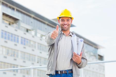 arquitecto: Retrato de la sonrisa Arquitecto de sexo masculino con los modelos que gesticulan los pulgares arriba al aire libre
