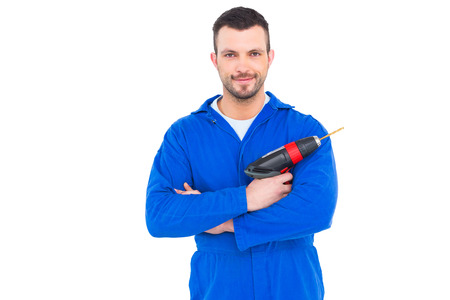 power drill: Portrait of confident handyman holding power drill on white background