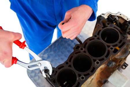 mechanician: Cropped image of male mechanic repairing car engine on white background
