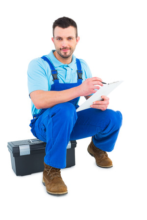 Plumber writing on clipboard while sitting on toolbox over white background photo