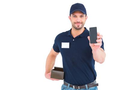 白い背景の上に携帯電話を示すハンサムな配達人 写真素材