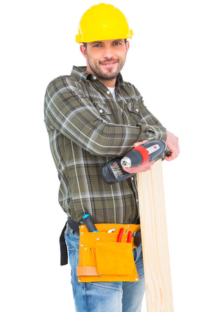 power drill: Carpenter holding power drill and wood plank on white background