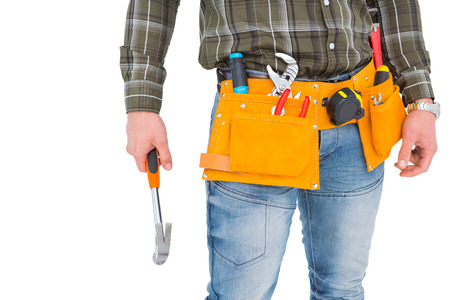 Manual worker wearing tool belt while holding hammer on white background photo