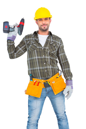 power drill: Handyman wearing tool belt while holding power drill on white background