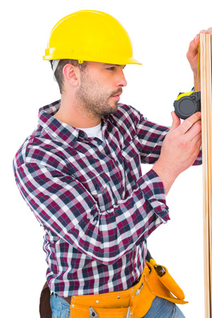 Handyman using measure tape on wooden plank on white background photo