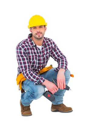 power drill: Crouching handyman holding power drill on white background
