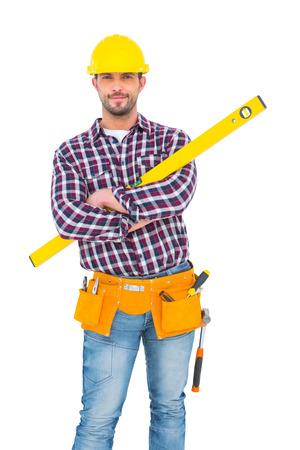 spirit level: Smiling handyman holding spirit level on white background