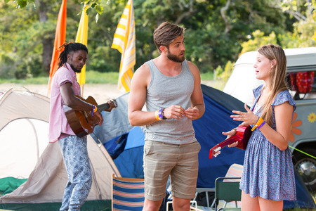 campsite: Hipsters having fun in their campsite on a sunny day Stock Photo