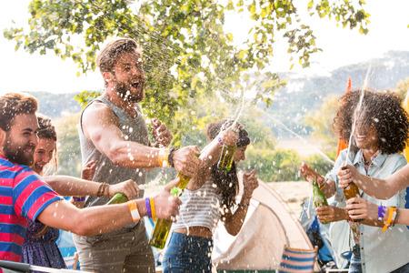 amicizia: Hipsters spruzzo birra sopra l'altro in una giornata di sole