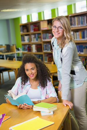 revision book: Student getting help from tutor in library at the university