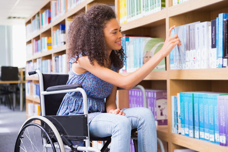 wheelchair: Smiling disabled student in library picking book at the university