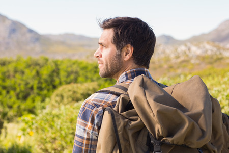 adventuring: Man hiking in the mountains on a sunny day