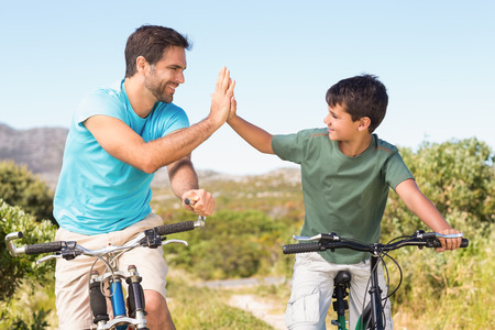 adventuring: Father and son on a bike ride on a sunny day Stock Photo