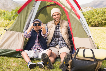 thumbsup: Father and son beside their tent on a sunny day Stock Photo